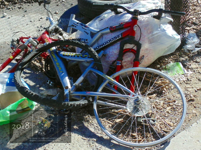 Already partly stripped two broken bikes perhaps, still contain some useful parts before garbage truck arrives.