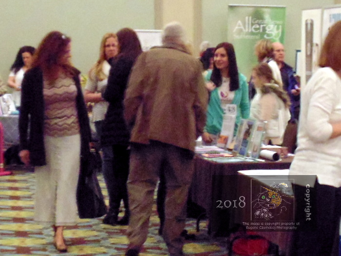 In Holiday Inn's main floor exhibition hall attendees ask one Health and Wellness exhibitor to elaborate on her special product or service.
