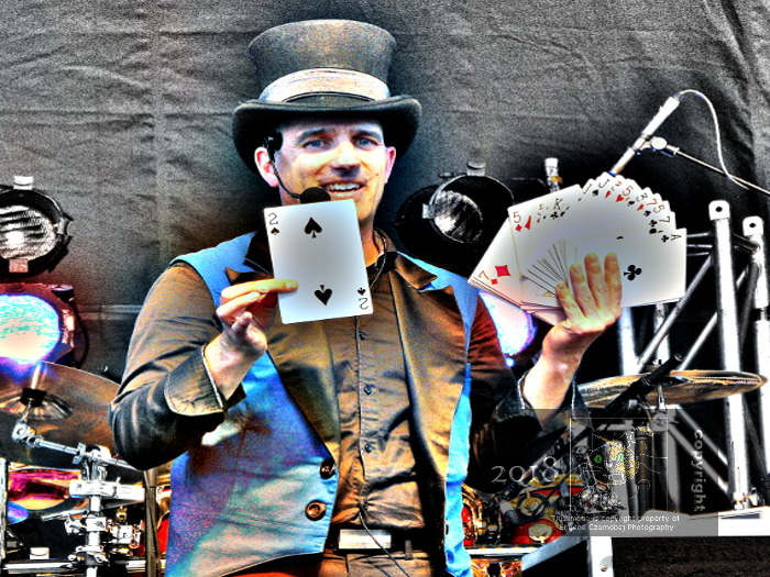 """Hocus pocus, Abra cadabra..look nothing up my sleeve"" followed by lots of banter magician's right hand brushes against held card deck pulling out two of spades."