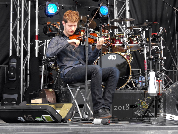Member of French Canadian trio plays fiddle performing Quebecois traditional music involving plenty of frantic footwork during Fete nationale.