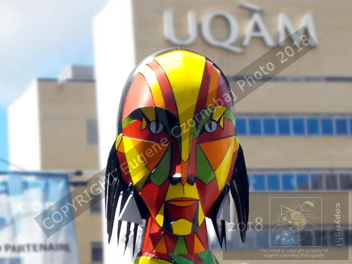 "Huge Indigenous puppet in traditional Iroquois ""war paint"" hovers its back to UQAM during Montreal's 28th First Nations Festival."